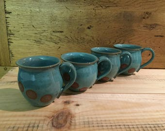 Four green and brown spotty coffee or tea mugs