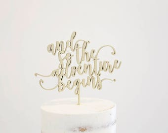 And So The Adventure Begins calligraphy quote wood laser cut cake topper for wedding, party, birthday, baby shower - gold or natural wood