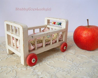 Vintage wooden doll bed on wheels, 1950s shabby white doll crib, doll cot with bedding, 5 by 3 inches, old dollhouse crib