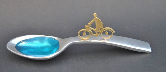 Decoration item, handmade. Aluminum spoon and brass figures. The color inside the spoon is made of glass.