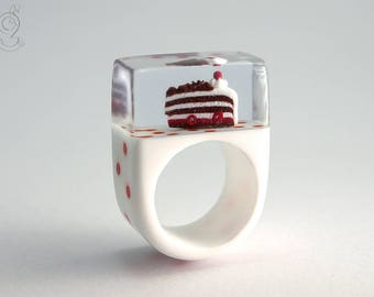 Cherry in the pie – Sweet gateau ring with a piece of black forest cake on a white ring with red polka dots made of resin for all gourmets