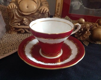 Deep red Aynsley corset cup and saucer .