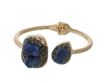 Gold tone hinge bangle bracelet with pyrite and sodalite stones