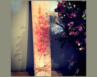 Coral and gold feather art on reclaimed wood