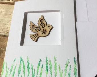 Handmade card with wooden bird embellishment and green stamped rushes.