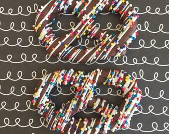 chocolate covered pretzel topped with rainbow nonpareil drizzle •two dozen
