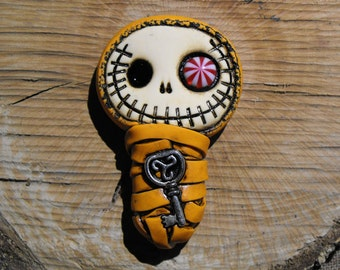 Friendly baby mummy bandaged in orange. Creepy and cute skull with a candy eye and a celtic key inside his body. Brooch or magnet
