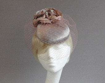 Silver and dusty pink hat with beaded edge , handmade flowers and two birdcage veiling's on comb