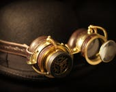 Steampunk goggles in dark brown leather and brass with folding loupe and monocle style eyepiece and embossed decoration