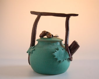 "Teapot, hand thrown porcelain with ""twig"" handle and leaf decoration, matte green and white glaze,functional"