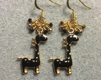 Black spotted enamel giraffe charm earrings adorned with tiny dangling black and gold Chinese crystal beads.