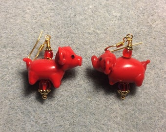 Red lampwork pig bead earrings adorned with red Czech glass beads.