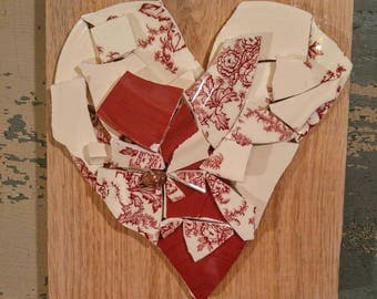 Broken and beautiful mixed media, wall mounted heart collage with broken ceramics in red, Ivory, and red Floral.