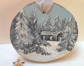 Winter woodland and cabin on wood slice