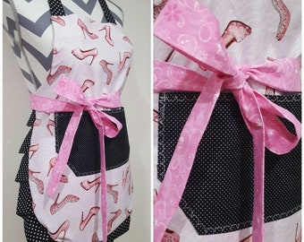 Youth apron. Girl's apron. Light pink w/ high heels on main. Black polka dots on pocket. Black w/ white mini polka dots on ties & frills.