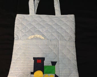 Four piece baby diaper bag with a bib, burp cloth, and decorative pillow, vintage.