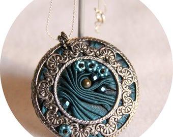 Collier médaillon en soie shibori bleu et contour argent, collier textile en soie bleu teal et argent, collier bleu paon en soie et cristal