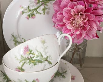 A Pair of Limoges Cups, Saucers and Cake Plates Decorated with a Pink Thistle Pattern