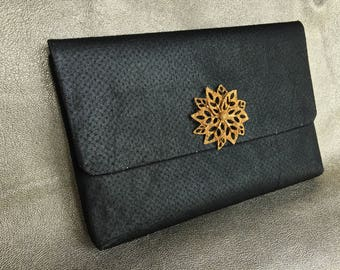Simple black clutch with slight sparkle embellished with stamped vintage gold tone brooch