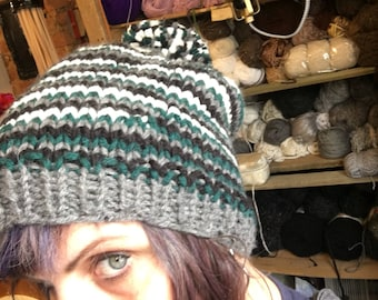 Slouchy handknit striped hat in our favorite teams colors . Warm and soft with a pompom to boot!