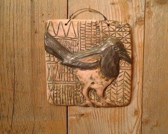 Magpie ceramic tile with hand drawn patterned background on weathered whitewash finish fired on hand pressed terra cotta tile.