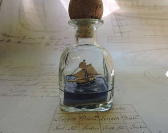 Sloop, Ship in a bottle sailing on a dark blue sea