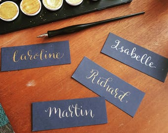 Beautiful hand calligraphy gold / silver on navy wedding name place cards.