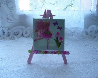 A frame with a fairy, tulips and butterflies on her easel for a girl