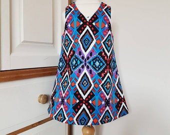 Bright geo print pinafore dress available in ages 6 months to 6 years