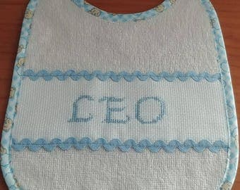 Personalized bib with embroidered cross-stitch name