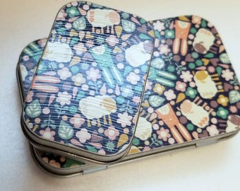 Large hinge tin and Medium hinge tin Duo. . . Bunnies and sheep and flowers o my. Great for the plane ride.