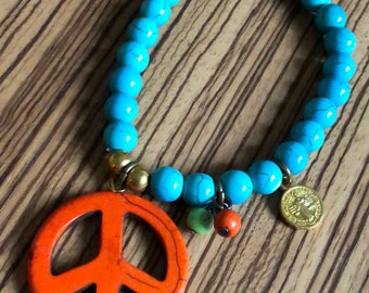 Orange peace sign with gold coin bracelet