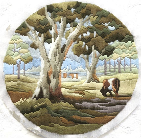 Completed embroidery on canvas, long stitched country scene of large trees and grazing cows, earthy tones, circle, 11 inches / 28 cm across