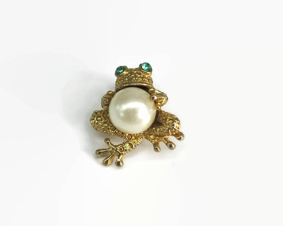 Vintage frog brooch, frog with green crystal eyes holding large lustrous faux pearl, gold tone metal, circa 1960s