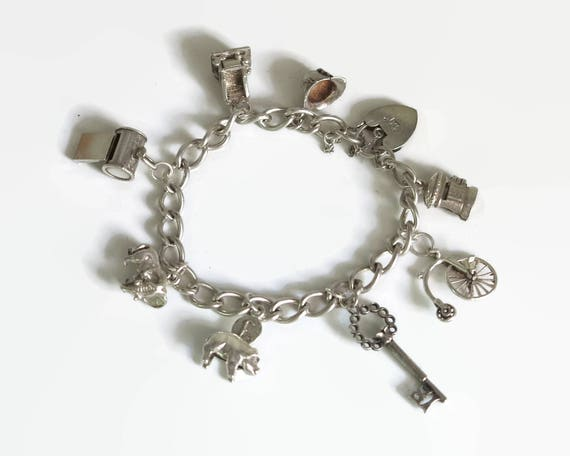Sterling silver bracelet with 8 charms, padlock closure, safety chain, curb link chain, larger charms, 8 inches / 20.5 cm, 35.66 grams