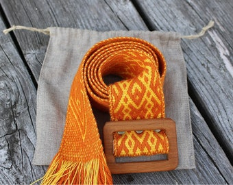Handmade woven belt with ornamental pattern and wooden buckle