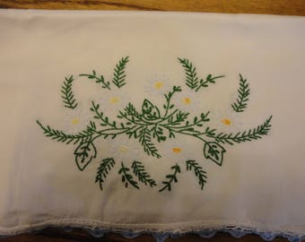 A vintage pillow case with a spray of daisies