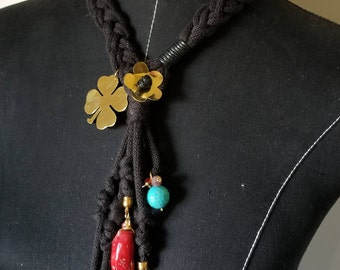 Long necklace with black woven drawstring tie and variety of charms