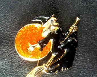 Vintage Halloween brooch, witch riding broomstick, black and orange enamel