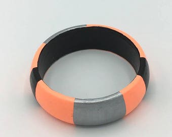 Handmade  bright geometric wooden bangle in salmon pink, silver and black