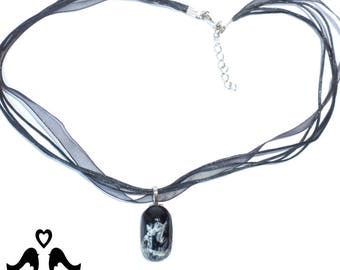 Black oval pendant with white marbling design on black organza ribbon necklace