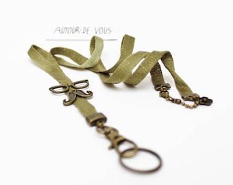 """Cordon porte-clés fantaisie """"moustache à lunettes"""" avec ruban coloré vert satiné et breloques en métal bronze"""