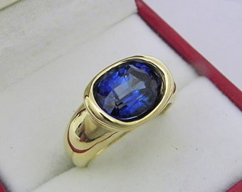 AAAA  Blue Sapphire Man Made 3.93 carats  10 x 8.0mm in 14K Yellow gold bezel set ring. 0250