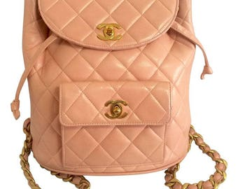 Vintage CHANEL quilted pink lamb leather backpack with golden chain straps and CC closure. Classic and popular bag. Must have.