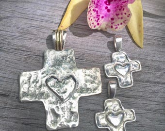 Two tone cross with heart pendant. Sterling silver and 18 goldfield.