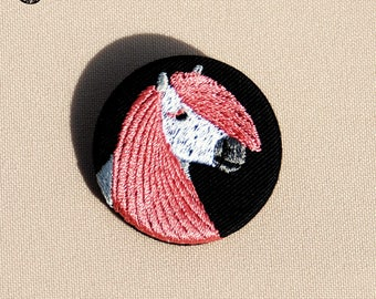 Small pin wearing a Pink Pony