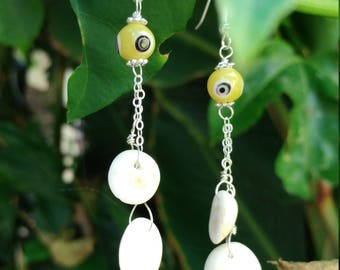 Earrings of glass evil eye beads and operculum (cats eye) shell on sterling silver