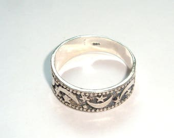 Sterling Silver Ring marked 925. Terrestrial stars and half moons suround this ring. Size 8. In good used condition.