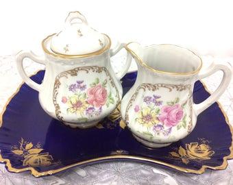 Vintage Porcelaine de France, creamer and sugar bowl adorned with flowers and ornate gild.