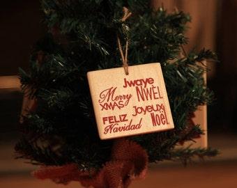 Christmas wooden decoration for hanging on Christmas tree - Joyeux Noël, Jwaye Nwèl, Feliz Navidad, Merry Xmas - Christmas bauble